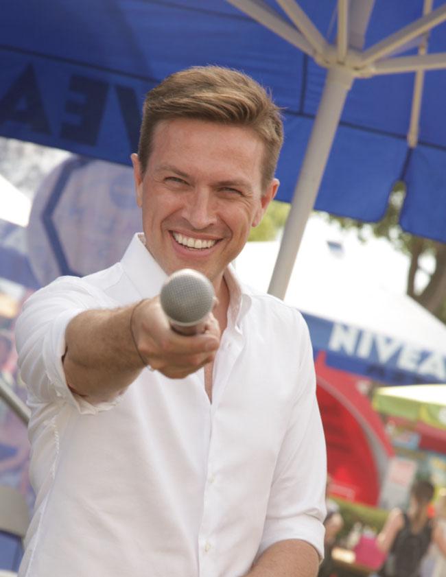 Rober Steiner hält ein Mikrofon in Richtung Kamera auf einem Event